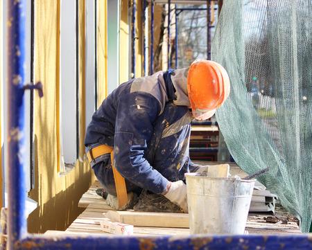 L'ouvrier fait le bardage des fenêtres dans le bâtiment restauré de la ville, coupe la tôle pour la pente avec des ciseaux Banque d'images - 78110536