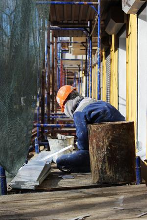 L'ouvrier fait le bardage des fenêtres dans le bâtiment restauré de la ville, coupe la tôle pour la pente avec des ciseaux Banque d'images - 78160257