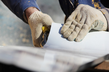 The worker makes the sladding of windows in the restored building in the city, cuts the metal sheet for the slope with scissors Stock Photo