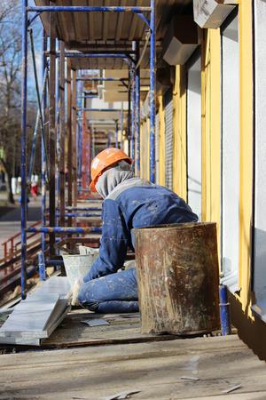 L'ouvrier fait le bardage des fenêtres dans le bâtiment restauré de la ville, coupe la tôle pour la pente avec des ciseaux Banque d'images - 78111349