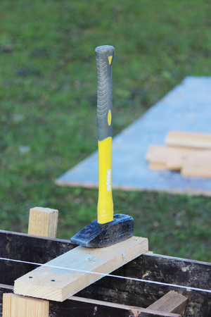 Construction tool hammer with a yellow handle lies on the formwork Stock Photo