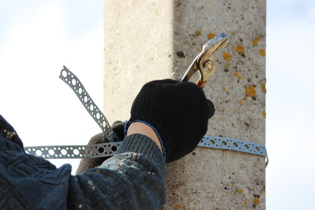 sign post: Worker affixes a metal chrome clamp to a post for hanging a road sign