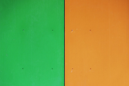 The wall of the house, trimmed with colorful panels, painted in bright colors. Green and orange