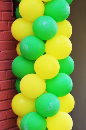 Multicolored yellow and green balloons adorn the entrance to the cafe Stock Photo - 79540952