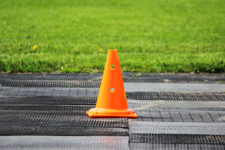 Plastic orange signal cone stands at the stadium in preparation for the competition for lifting weights.