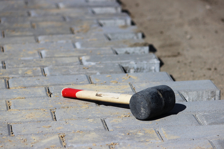 A professional hammer for fitting paving slabs to each other Stock Photo