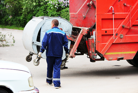 worker loads rubbish bin at a recycling machine. Stock Photo