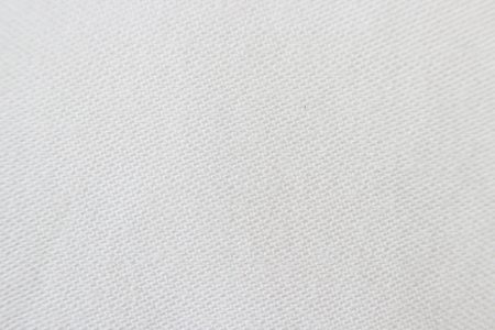 joining: Macro texture of light beige fabric with machine seam.