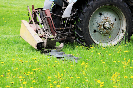 The tractor with a special nozzle automatically mows the grass on an urban lawn.