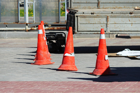 plastic signaling traffic Cones limit from people the place of installation of a glass advertising stand where the crane works