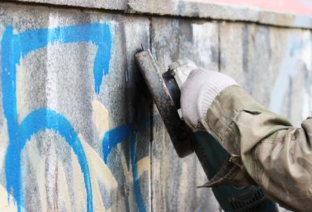 Enlèvement de graffiti sur un mur de béton d'un passage souterrain à l'aide d'une meuleuse d'angle. Banque d'images - 80624024
