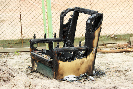 burned out: The burnt-out armchair is standing on the street. Danger of smoking. Stock Photo