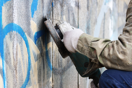 pamper: Removal of graffiti on a concrete wall of an underground passage with the help of a angle grinder.