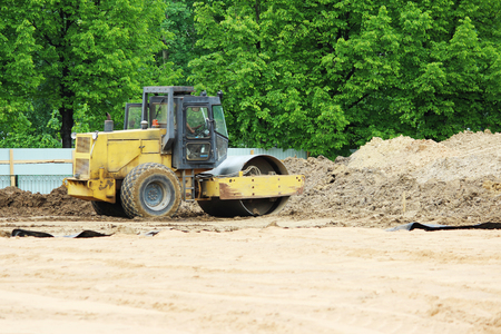 compactor is compacting the surface of the earth. Construction of the city stadium
