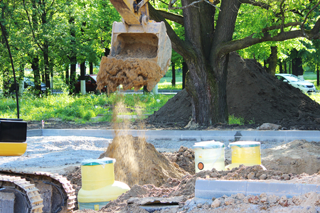 baffle: Excavator digs to plastic tank gas oil catcher in the ground during the construction of a car park for tourist buses, Russia Stock Photo