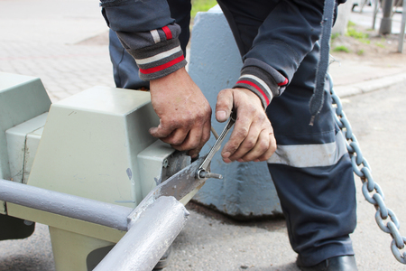 The worker replaces the broken traffic light with a working traffic light. Unscrewing parts with lamps from fastening with a spanner