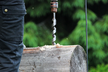 The worker collects the frame and drills a hole in a log for dowel using a drill when building a wooden house. Stock Photo