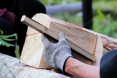 The worker makes a marking on the log before the building of the blockhouse and uses wooden dowel as a ruler markup before working to hacket.