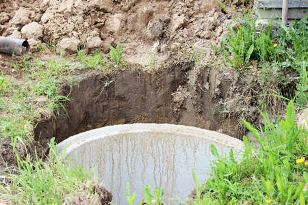 Well for water extraction. The construction of a village well for the extraction of water with the help of several concrete rings laid in a pit of earth. Stock Photo