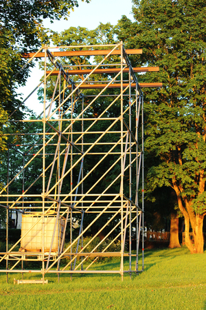 clamped: Metal structure in the form of a frame for attaching musical columns and a screen for broadcasting events in the park. Stock Photo
