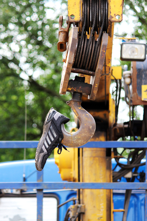 Protective cover on the hook from the lifting crane, built into the truck in the form of a sneaker Stock Photo