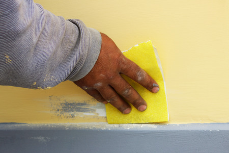 Work plasterer processes the wall of the house with sandpaper. Elimination of poor-quality work before re-coating with paint.