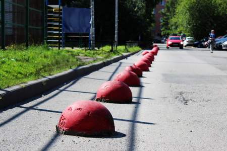 Ball-shaped red concrete pedestal near the house beside the road against the entry of vehicles