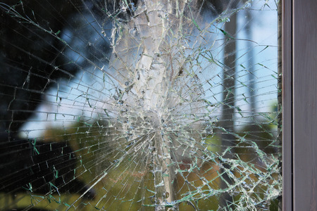 Vandals smashed the glass at a bus stop in the city. Stock Photo