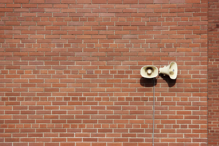 Red brick wall of a residential building and two loudspeakers. Stock Photo