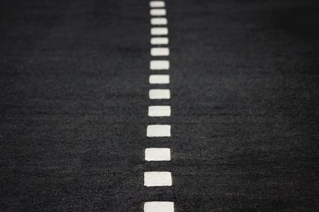New white intermittent road markings on black asphalt. 版權商用圖片