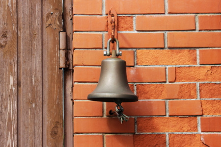 A large bell next to the door, replacing the doorbell. the bell Welcome. Ring the bell.