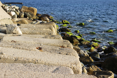 Large concrete rectangular blocks to protect the shore from erosion lie in the sea. Enclosure of railroad tracks. Stock Photo