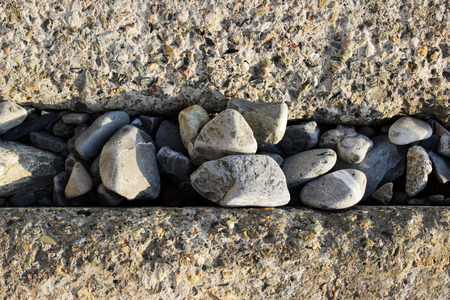 Large concrete rectangular blocks to protect the shore from erosion. Enclosure of railroad tracks. Between the blocks are poured a lot of granite stones. Stock Photo