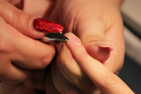manicurist at training courses shows students how to handle nails with the help of nippers cuticles before applying shellac Stock Photo