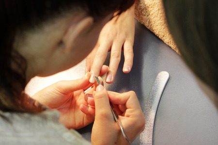 A student at the training courses of a manicure prepares the hand of a lady client with tool for scraping scraper before applying shellac. Stock Photo