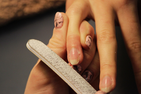 A student at the training courses of a manicure prepares the hand of a lady client with a file before applying shellac