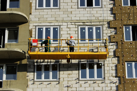 work with yellow front two suspended cradle with workers on a newly built high-rise building Stock Photo