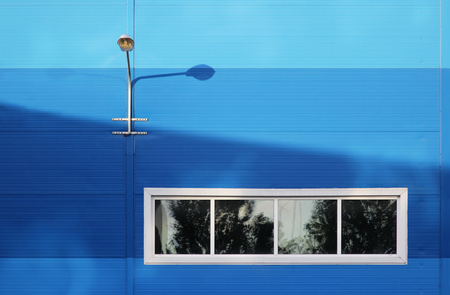 The surface of the blue wall of a large office building. There are four windows. wall lamp for street lighting.