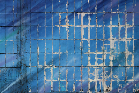 The wall of a residential house, covered with tiles and painted with blue paint. Part of a large graphite under the open air