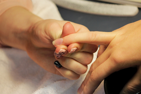 A student at training courses assesses the hand of a lady client before preparing for a manicure. Stock Photo