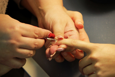 Manicurist at the training courses of a manicure prepares the hand of a lady client with tool for scraping scraper before applying shellac