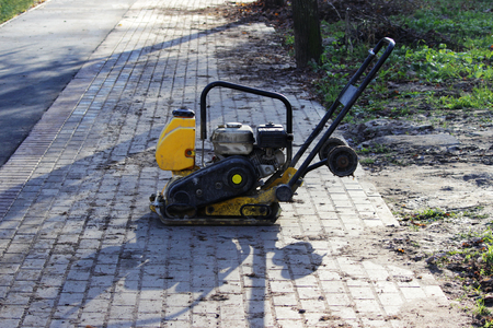 Small yellow compactor standing on new gray pavement.