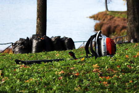 industrial vacuum cleaner lies on the grass against a background of black trash bags filled with leaves. Stock Photo