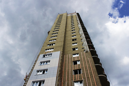 newly built high-rise building with insulating ecological modern panels on a blue sky background.