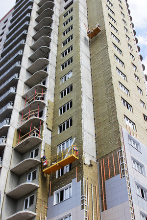 worker in yellow front suspended cradle on a newly built high-rise building