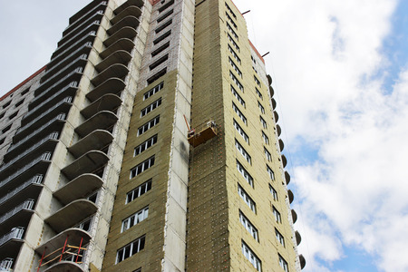 worker in yellow front suspended cradle on a newly built high-rise building. Stock Photo