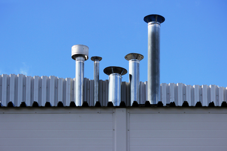 Four chimney pipe from metal on the roof of the house Stockfoto