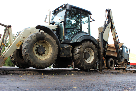 Truck strong outrigger stabilizing legs extended. Tractor on extended outriggers for better stability digging a bucket of road for repair. reportage photography.