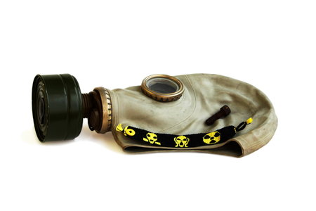 Isolated trophies of the stalker: old Russian gas mask, rusty nail and yellow-black baubles on a white background