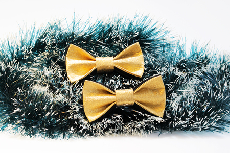 two festive gold butterfly bow tie against a background of green Christmas tree tinsel. Stock Photo